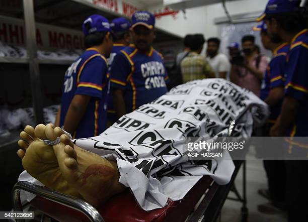 Graphic content / Pakistani volunteers place the body of Sufi musician Amjad Sabri who was killed in an attack by unknown gunmen at a morgue in...