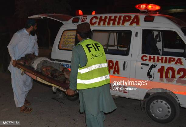 Graphic content / Pakistani volunteers use a stretcher to carry a victim towards an ambulance after a blast in Quetta on August 12 2017 A powerful...