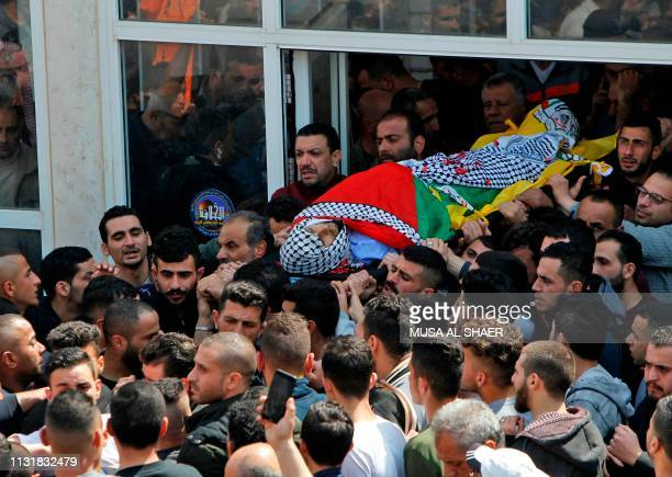 Graphic content / Palestinian mourners carry the body of 26yearold Ahmed Manasara during his funeral in the village of Wadi Fukin west of Bethlehem...