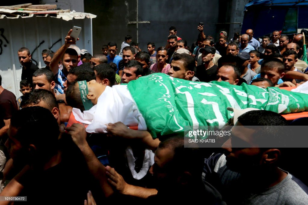 Graphic content / Palestinian mourners carry the body of Muadh al-Suri, aged 15, who was killed in clashes with Israeli forces the day before, during his funeral in Nuseirat camp, in central Gaza Strip, on August 4, 2018. - A Palestinian teen died of his wounds on August 4 a day after he was shot by Israeli troops during clashes on the Gaza border, the territory's Hamas-run health ministry said. Muadh al-Suri, 15, was shot in the stomach on August 3 in central Gaza, ministry spokesman Ashraf Al-Qudra said, raising the number of Palestinians killed by Israeli fire during those clashes to two, with over 200 wounded.