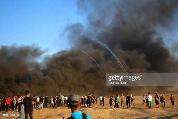 Graphic content / Palestinian protesters gather in the smoke billowing from burning tyres as Israeli forces launch tear gas canisters at the...