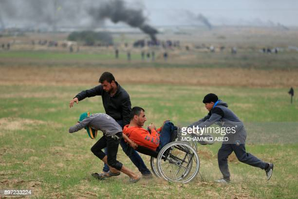 Graphic content / Palestinian protesters help a man in a wheelchair during clashes with Israeli soldiers near the border fence east of Gaza City on...