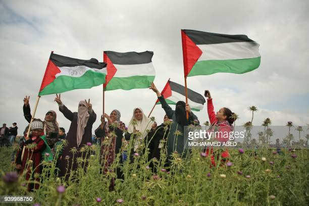 Graphic content / Palestinian women wave Palestinian flags and flash the victory gesture during a protest near the border with Israel east of Jabalia...