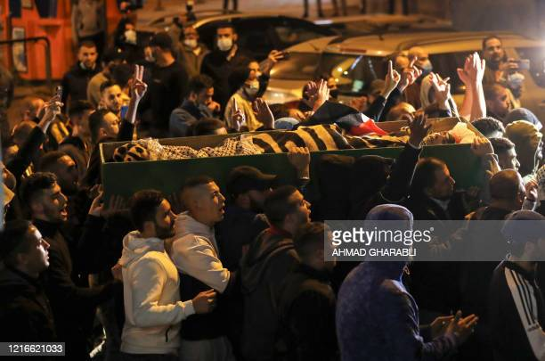 Graphic content / Palestinians carry the coffin of Iyad Hallak, a disabled Palestinian man who was shot dead by Israeli police after they mistakenly...