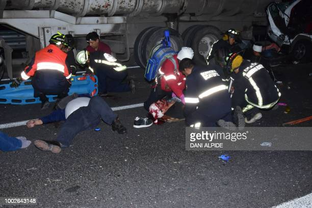 Graphic content / Paramedics work at the scene where a passenger transport vehicle crashed into a truck in the highway linking Mexico City and...