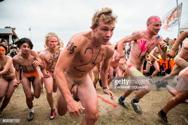 Participants compete during the annual Naked Run at the camp site of the Roskilde Festival on June 29 2017 in Roskilde some 30 km west of Copenhagen...