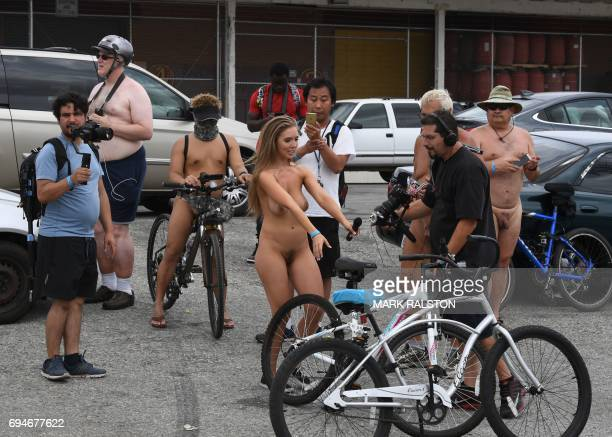 Graphic content / Participants take photos of a female reporter during an interview at the Los Angeles leg of the World Naked Bike Ride in Los...