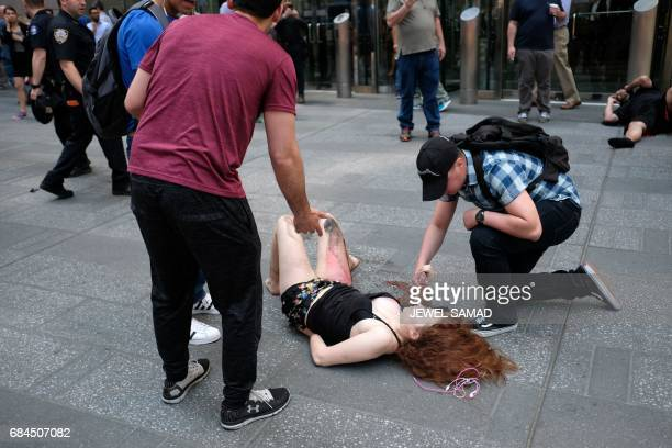 Graphic content / People attend an injured woman after a car plunged into her in Times Square in New York on May 18 2017 A car plowed into a crowd of...
