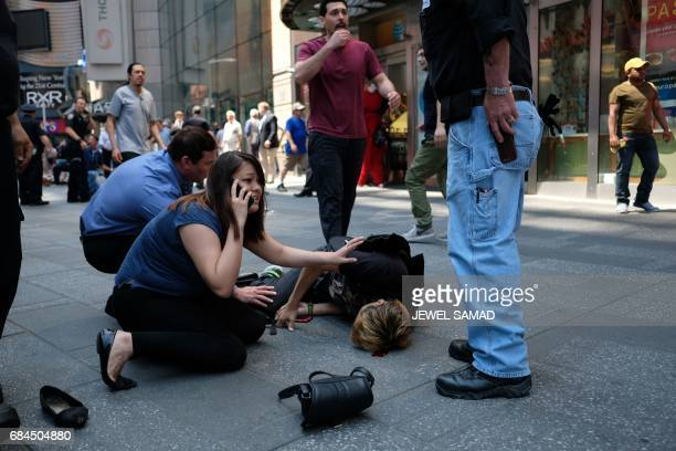 Graphic content / People attend to an injured man after a car plunged into him in Times Square in New York on May 18 2017 A car plowed into a crowd...