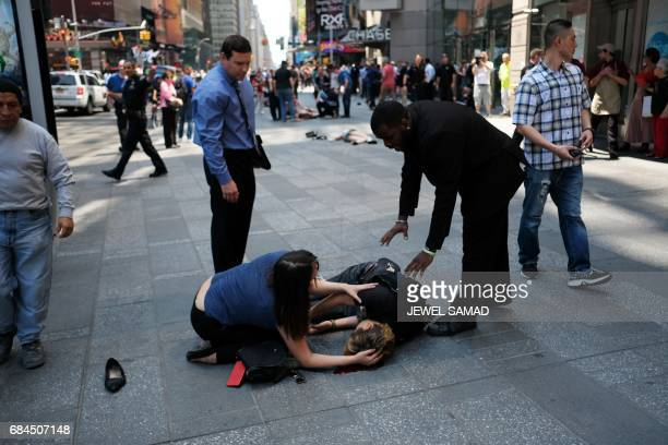 Graphic content / People attend to an injured person moments after a car plunged into them in Times Square in New York on May 18 2017 A car plowed...
