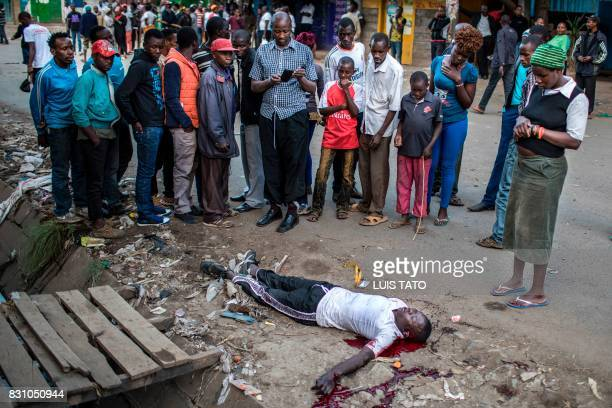 Graphic content / People gather around a man belonging to the Luo tribe lays motionless on the ground after being beaten by the mob on August 13 2017...
