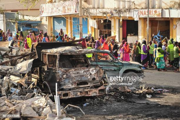 Graphic content / People gather near burnt vehicles a day after a truck bomb exploded in the centre of Mogadishu on October 15 2017 A truck bomb...