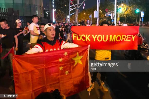 Graphic content / People hold the Chinese flag and a protest banner in reference to a controversial tweet last week by Rockets general manager Daryl...
