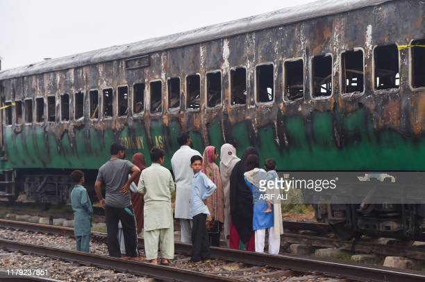 Graphic content / People look at the burntout train carriages a day after a passenger train caught on fire in Rahim Yar Khan on November 1 2019...