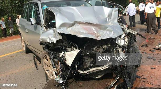 Graphic content / People look at the damaged car carrying Cambodian Prince Norodom Ranariddh and his wife Ouk Phalla shown in the foreground...