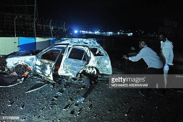 Graphic content / People look at the wreckrage of a car following an attack in the center of Mogadishu on February 26 2016 At least 12 people were...