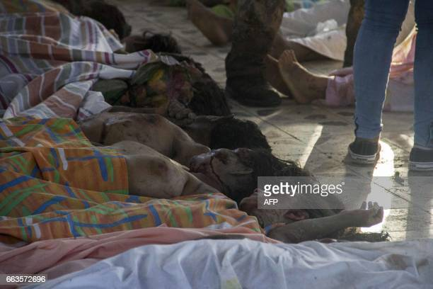 Graphic content / People look for family members among the bodies of victims of mudslides following heavy rains at the cemetery in Villagarzon...