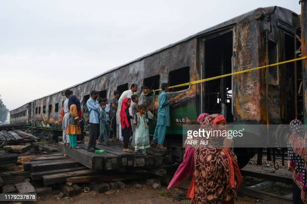 Graphic content / People looks at the burntout train carriages a day after a passenger train caught on fire in Rahim Yar Khan on November 1 2019...