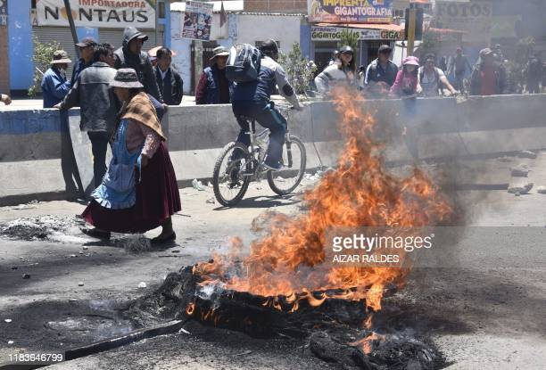 Graphic content / People pass next to a bonfire at a road blocked by supporters of Bolivia's President Evo Morales outside the Senkata fuel plant in...