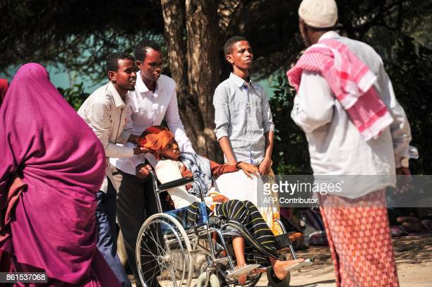 Graphic content / People pull in a wheelchair a woman injured in the explosion of a truck bomb in the centre of Mogadishu on October 15 2017 A truck...