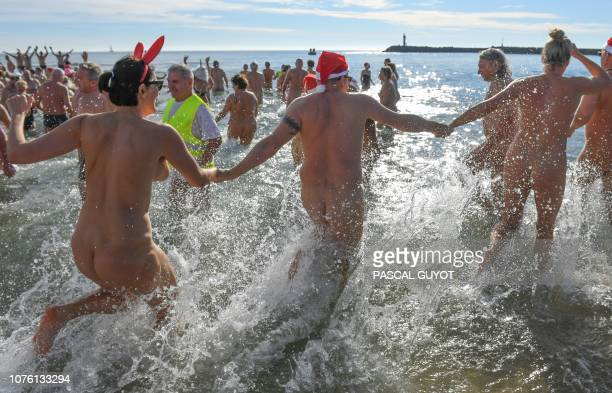 Graphic content / People run into the water as they take part in a traditional sea bath to mark the New Year's celebrations on a nudist beach in Le...