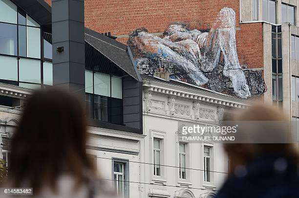 Graphic content / People stand in front of a mural featuring a woman masturbating on the side of a house in the Louise area of Brussels on October 14...