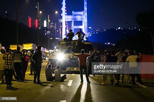 Graphic content / People take over a tank near the Fatih Sultan Mehmet bridge during clashes with military forces in Istanbul on July 16 2016...