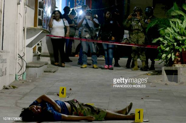 Graphic content / People take pictures of the crime scene where man was riddled with bullets in the historic neighborhood of the touristic city port...