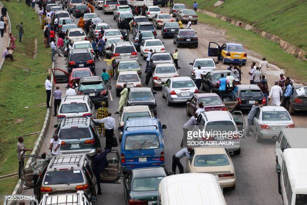 Graphic content / People wait next to their cars on the Abuja Nasarawa road due to clashes between Nigerian soldiers and members of Islamic Movement...