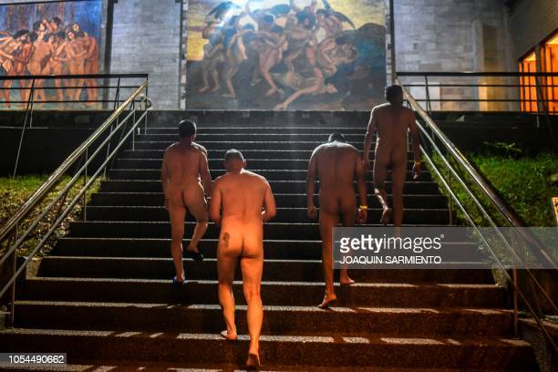 Graphic content / People walk in front of a mural by Colombian artist Pedro Nel Gomez during a special guided nudist visit of the exhibition The nude...