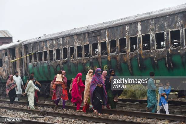 Graphic content / People walk past the burntout train carriages a day after a passenger train caught on fire in Rahim Yar Khan on November 1 2019...