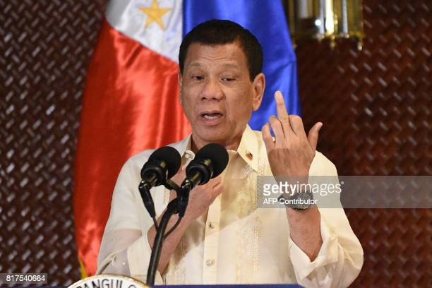 Graphic content / Philippine President Rodrigo Duterte gestures the middle finger in an address to military personnel to not give up their weapons so...