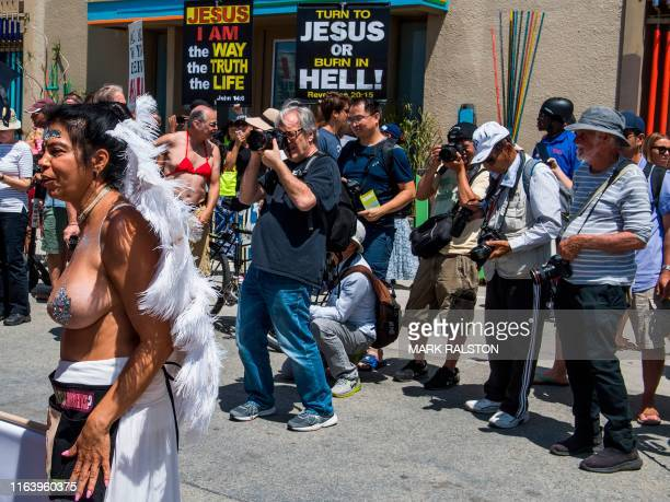 Graphic content / Photographers take pictures as GoTopless Day demonstrators march during their annual protest for women's rights in Venice Beach...