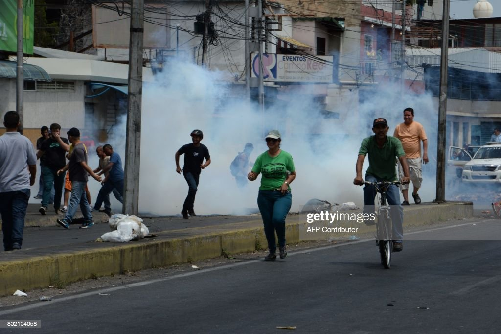 Graphic content / Police fire tear gas to scatter the crowd during lootings in Maracay, Venezuela on June 27, 2017. / AFP PHOTO / Federico Parra / GRAPHIC