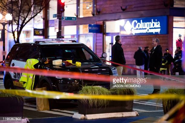 Graphic content / Police officers are pictured at the scene of a shooting that left one person dead and seven injured, including a child, in downtown...