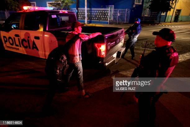 Graphic content / Police officers frisk a man during an operation in Tlaquepaque, Jalisco State, Mexico, on November 22, 2019. - AFP has mobilized...