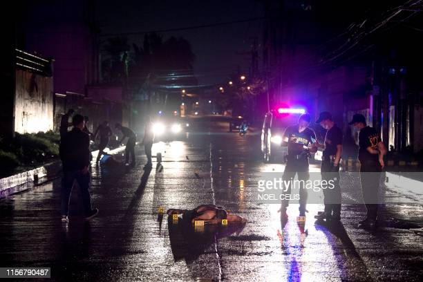 Graphic content / Police officers investigate a scene of a shootout as the body of a suspect lies on a street in Manila on July 20, 2019. - Three...