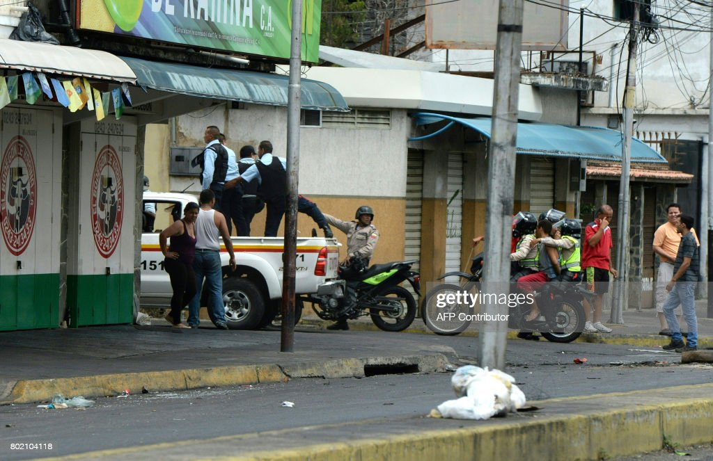 Graphic content / Police take a man into custody (on the motorcycle) during lootings in Maracay, Venezuela on June 27, 2017. / AFP PHOTO / Federico Parra / GRAPHIC