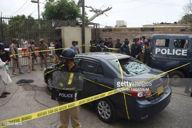 Graphic content / Policemen guard a car used by alleged gunmen outside the Pakistan Stock Exchange building in Karachi on June 29 2020 At least six...