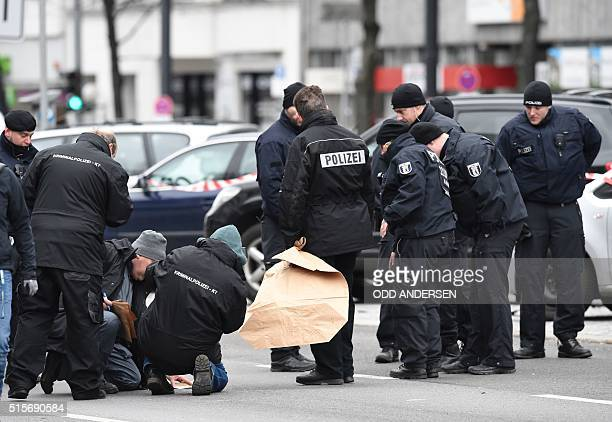 Graphic content / Policemen look for evidences near the wreckage of a car after a blast caused by an explosive device killed its driver travelling...