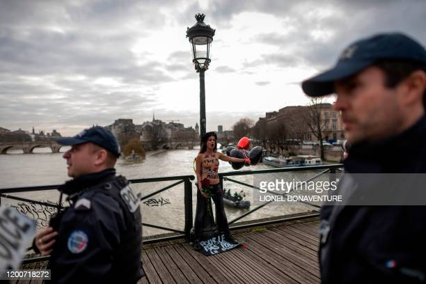 Graphic content / Policemen stand as a member of the feminist movement Femen is chained on the pont des Arts in Paris on February 14 2020 on...