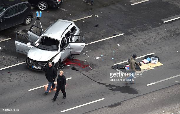Graphic content / Policemen stand near the wreckage of a car after a blast caused by an explosive device killed its driver travelling down a street...