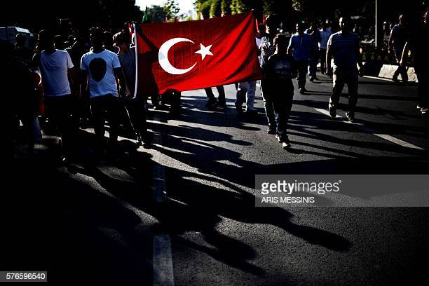 Graphic content / ProErdogan supporters wave national flags as the demonstrate in support to the government in Istanbul on July 16 2016 following a...