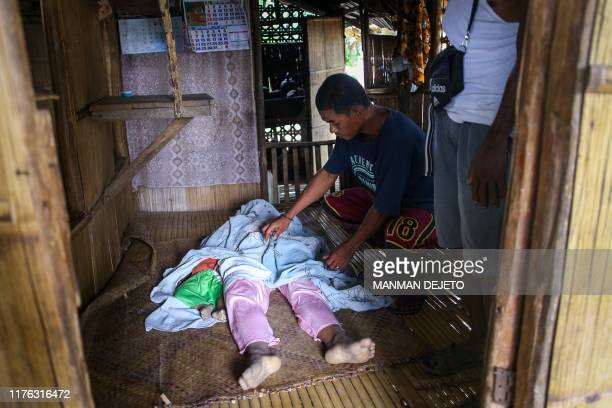 Graphic content / Relatives mourn over the bodies of Argel Abundo-Lakay and her nine-month-old son Jayjay Lakay who perished in a landslide triggered...