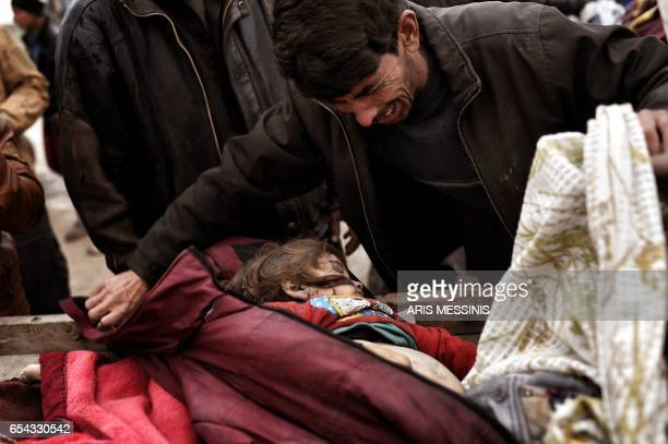Graphic content / Relatives mourn over the body on an Iraqi child killed in an airstrike targetting Islamic State group jihadists West Mosul on March...