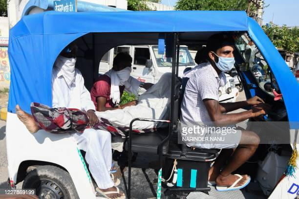 Graphic content / Relatives on an auto-rickshaw hold the dead body of Darshan Singh, who diedafter allegedly drinking spurious alcohol, at the Civil...