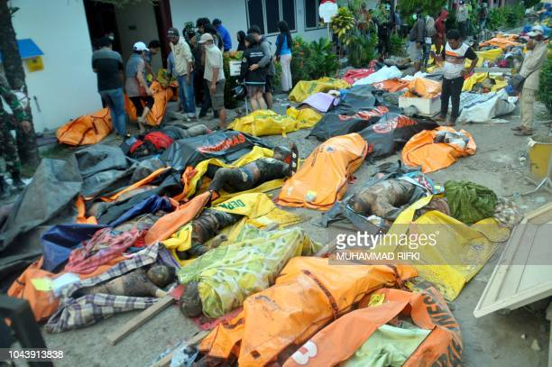 Graphic content / Rescue personnel prepare the bodies of the earthquake victims at the compound of a police hospital in Palu Indonesia's Central...