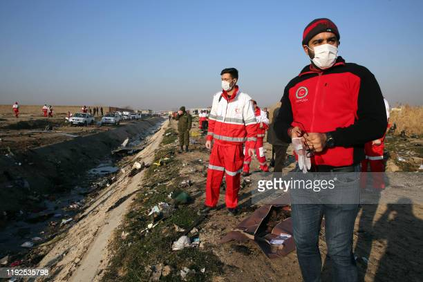Graphic content / Rescue teams recover a body after a Ukrainian plane carrying 176 passengers crashed near Imam Khomeini airport in the Iranian...