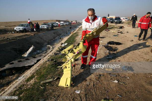 Graphic content / Rescue teams recover debris from a field after a Ukrainian plane carrying 176 passengers crashed near Imam Khomeini airport in the...
