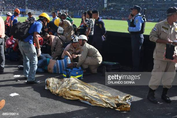 Graphic content / Rescue workers assist an injured fan of Honduran team Motagua next to the body of one of two supporters of the team who were killed...